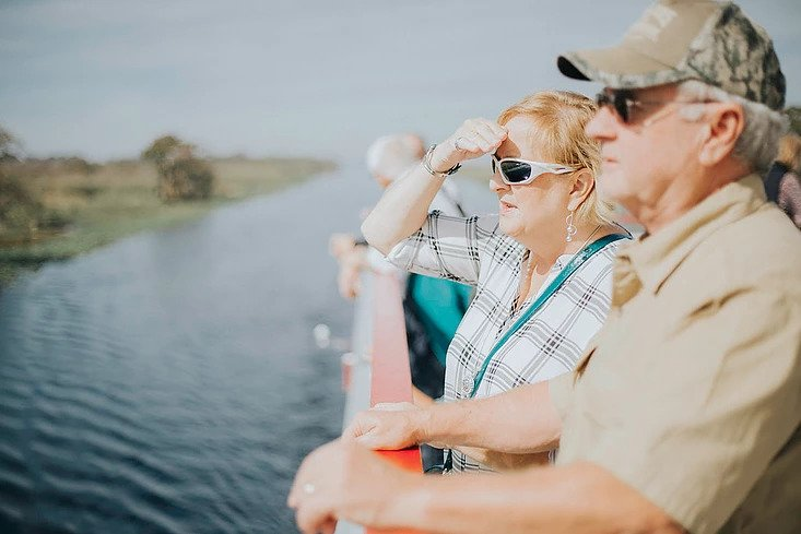 a couple looks for wildlife from the deck of the sternwheeler while on their lunch cruise from Sanford onan original orlando tours visit