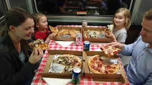 a family enjoys a pizza lunch on the royal pizza express train tour is included during an original orlando tours visit to historic mount dora florida