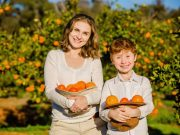 mom and son holding citrus freshly picked at u-pick citrus farm prior to monster truck tour while on original orlando tours